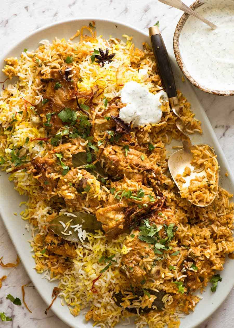 Chicken Biryani on a large serving platter, garnished with coriander with a side of minted yoghurt.
