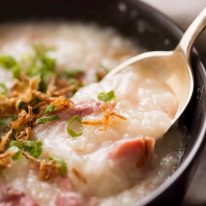 Close up of spoon scooping Chinese Ham Bone Rice Soup (Congee) out of a rustic brown bowl