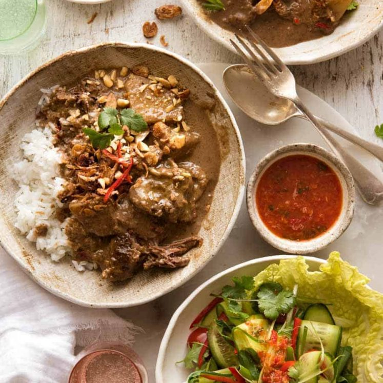 Overhead photo of two bowls with Massaman Curry on rice with a side salad, ready to be eaten