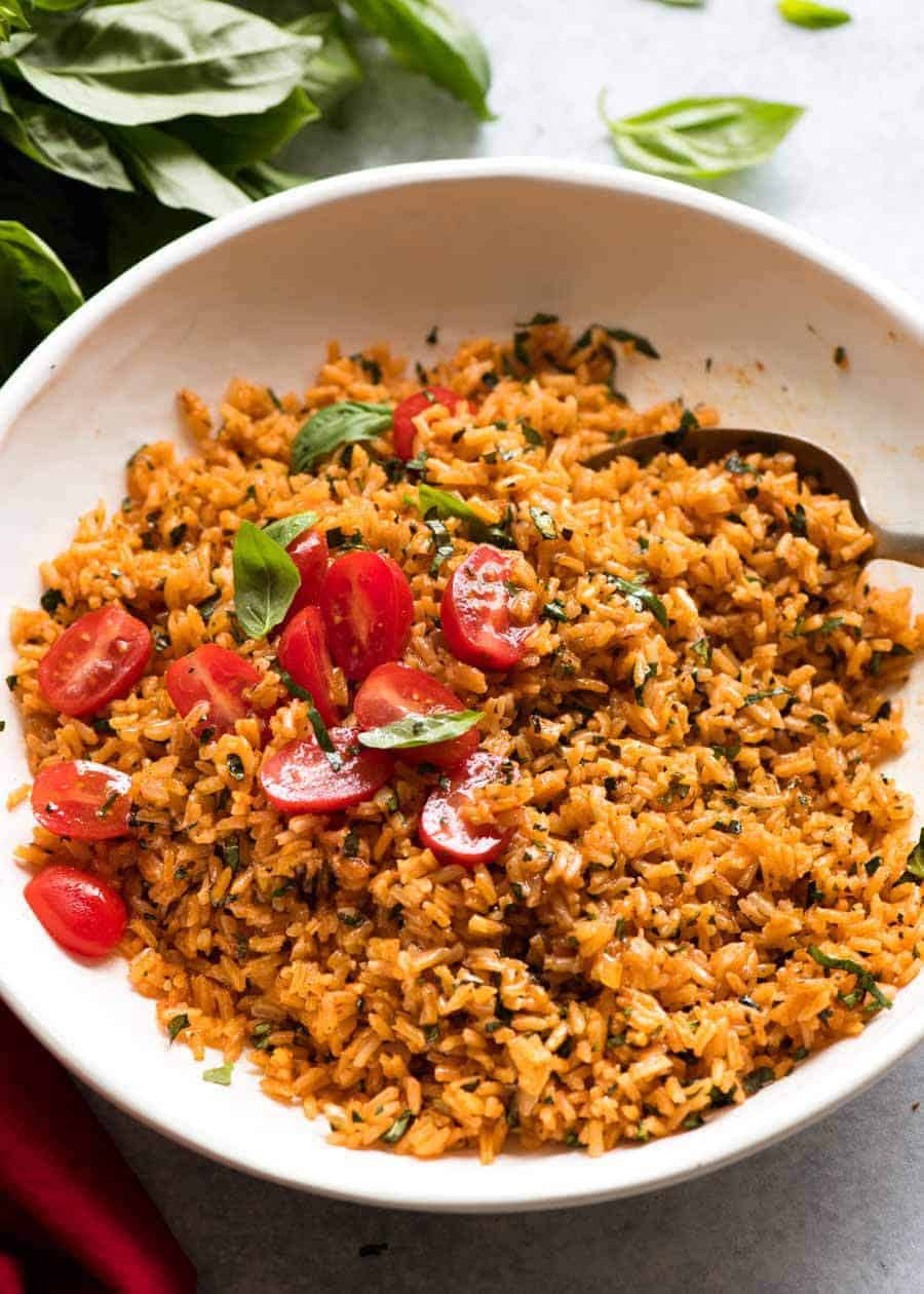 Pile of Tomato Basil Rice in a white bowl garnished with fresh tomato and basil, ready to be served
