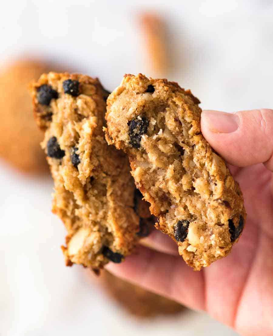 Close up of hand holding Healthy Oatmeal Cookies broken in half to show the chewy inside