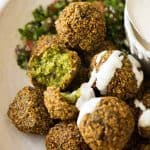 Close up of Falafels in a bowl drizzled with tahini sauce