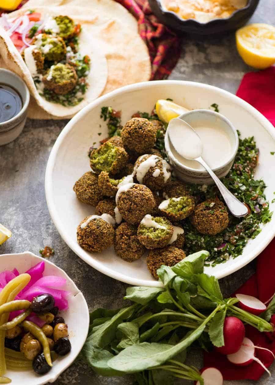 Falafels in a bowl with sides - tahini sauce, tabbouleh, hummus, pickles, wraps