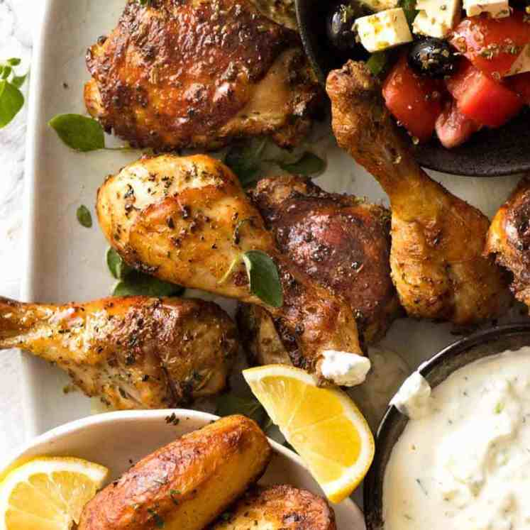 Greek Chicken on a plate with Greek Salad, Lemon Roasted Potatoes and Tzatziki on the side