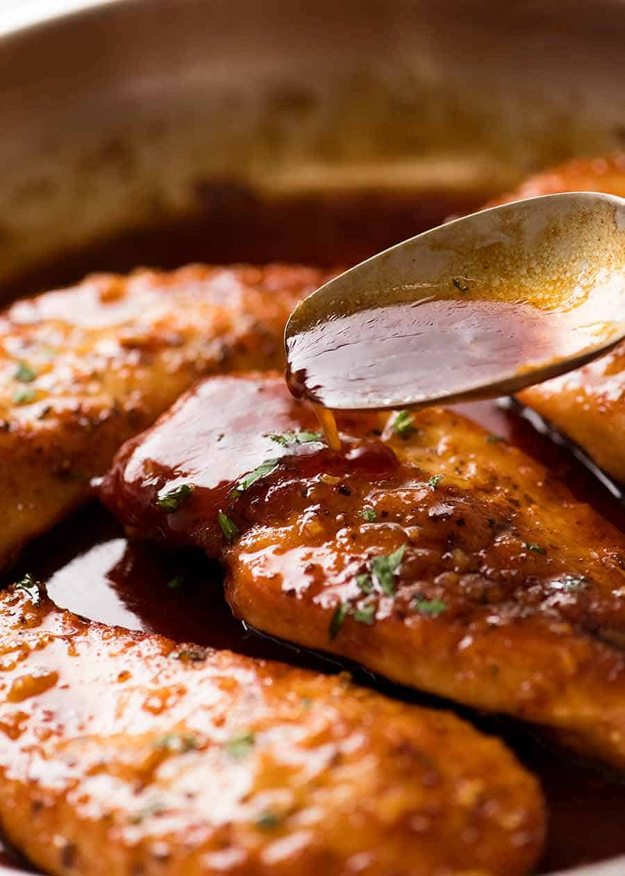 Spoon drizzling Honey Garlic Sauce over Chicken breast