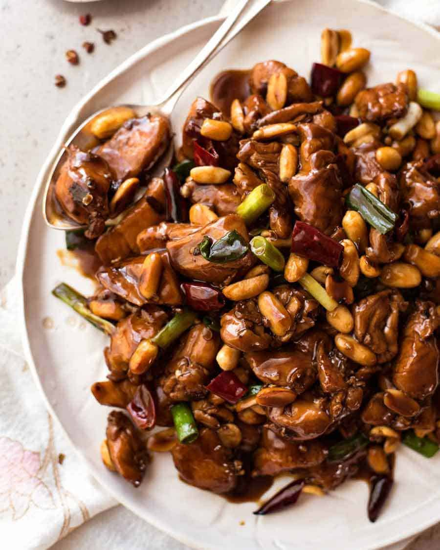 Overhead photo of Kung Pao Chicken on a rustic white plate, ready to be served