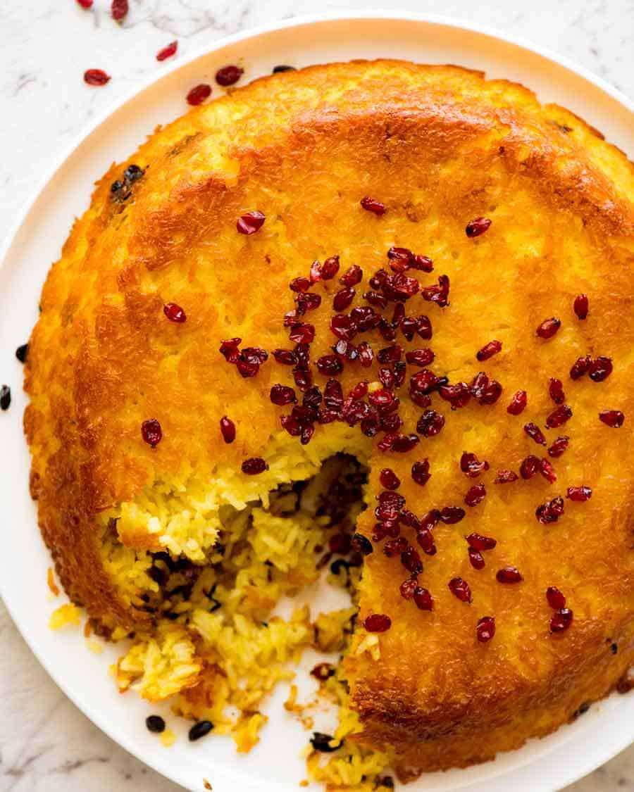 Overhead photo of Tachin Persian Saffron Rice sprinkled with barberries