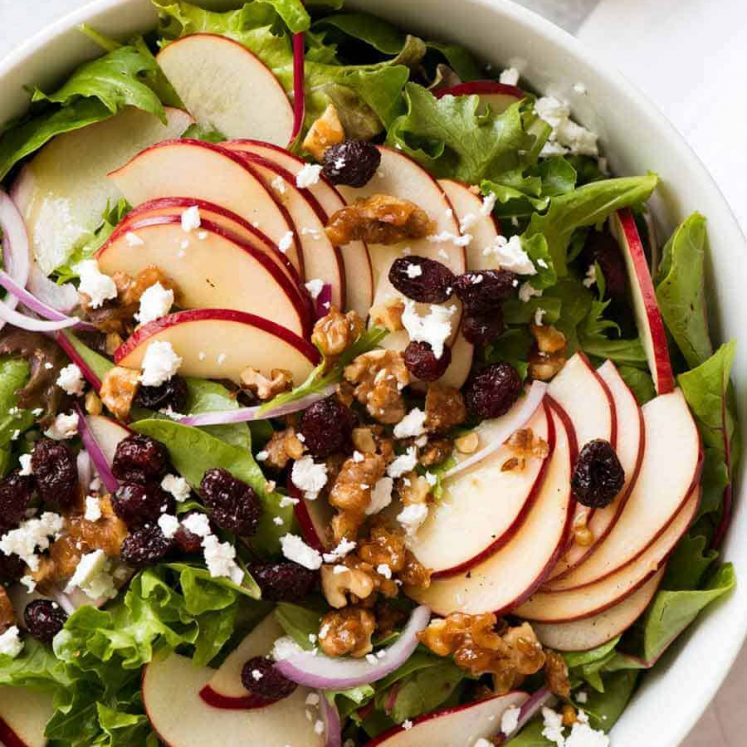 Overhead photo of Apple Salad with Candied Walnuts and Cranberries with vinaigrette dressing on the side
