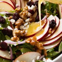 Vinaigrette being poured over Apple Salad with Candied Walnuts and Cranberries