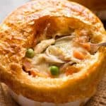 Close up of Chicken Pot Pie in a ramekin with puff pastry topping, made from scratch with uncooked chicken.