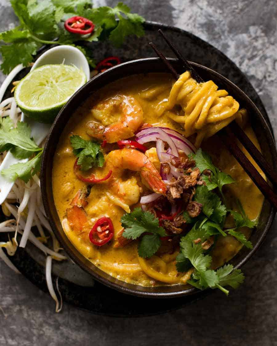 Overhead photo of Thai Coconut Soup with Shrimp/Prawns and Noodles in a black bowl, ready to be eaten