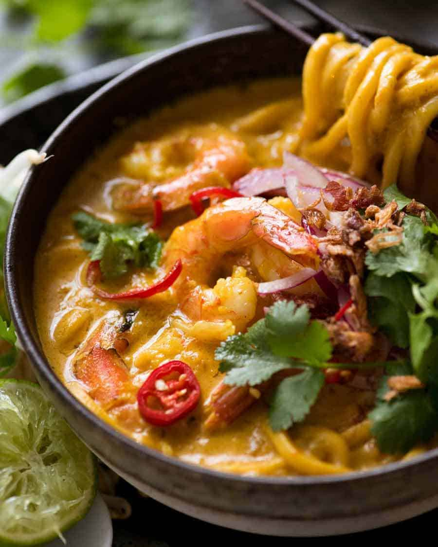 Thai Coconut Soup with Shrimp/Prawns and Noodles in a rustic bowl, ready to be eaten