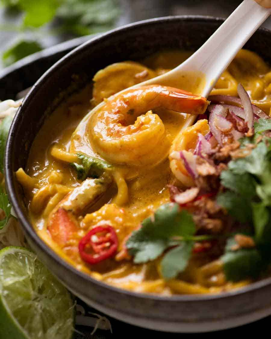 Close up of spoon scooping up Thai Coconut Soup with Shrimp/Prawns and Noodles