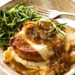 French Onion Smothered Pork Chops on mashed potato with a side of sautéed snow pea sprouts
