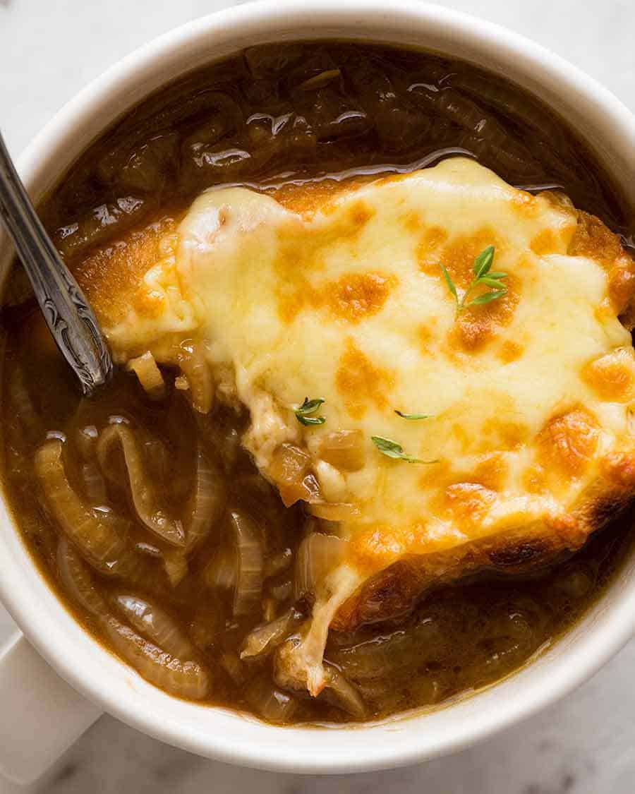 Close up overhead photo of French Onion Soup in a white bowl with a spoon