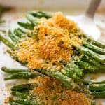 Close up of spatula scooping up Parmesan Roasted Green Beans