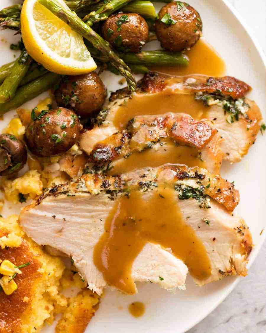 Slow Cooker Garlic Herb Turkey Breast dinner plate with creamy corn casserole, roasted mushrooms, and lemon garlic asparagus