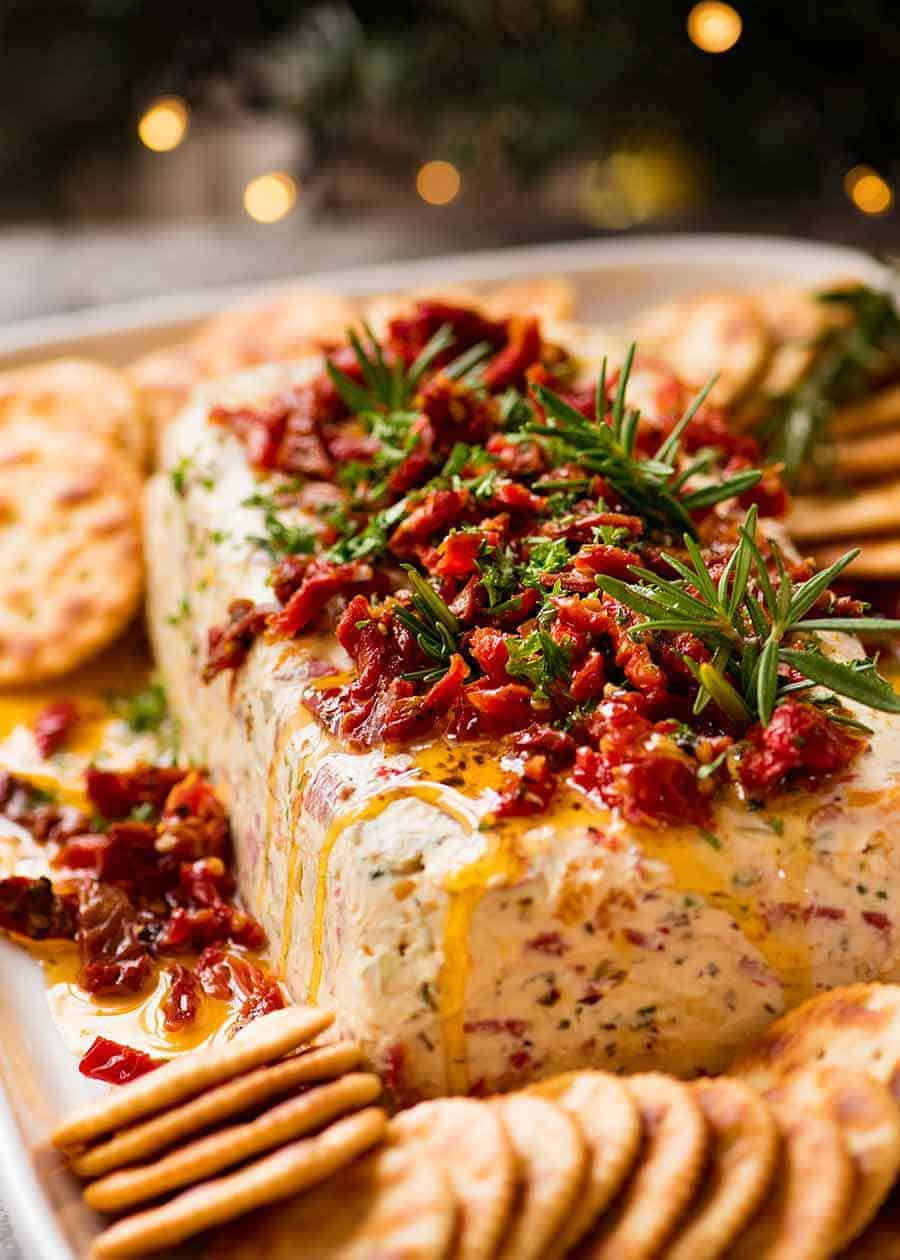Christmas Appetiser Italian Cheese Log with Christmas tree in background - festive appetizer for the holidays