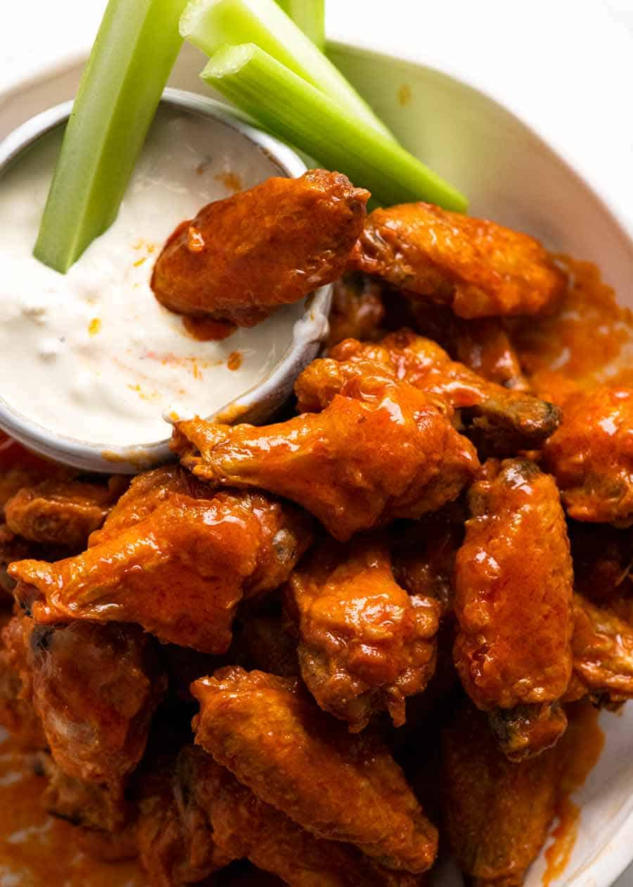 Pile of buffalo wings with blue cheese dip and celery sticks