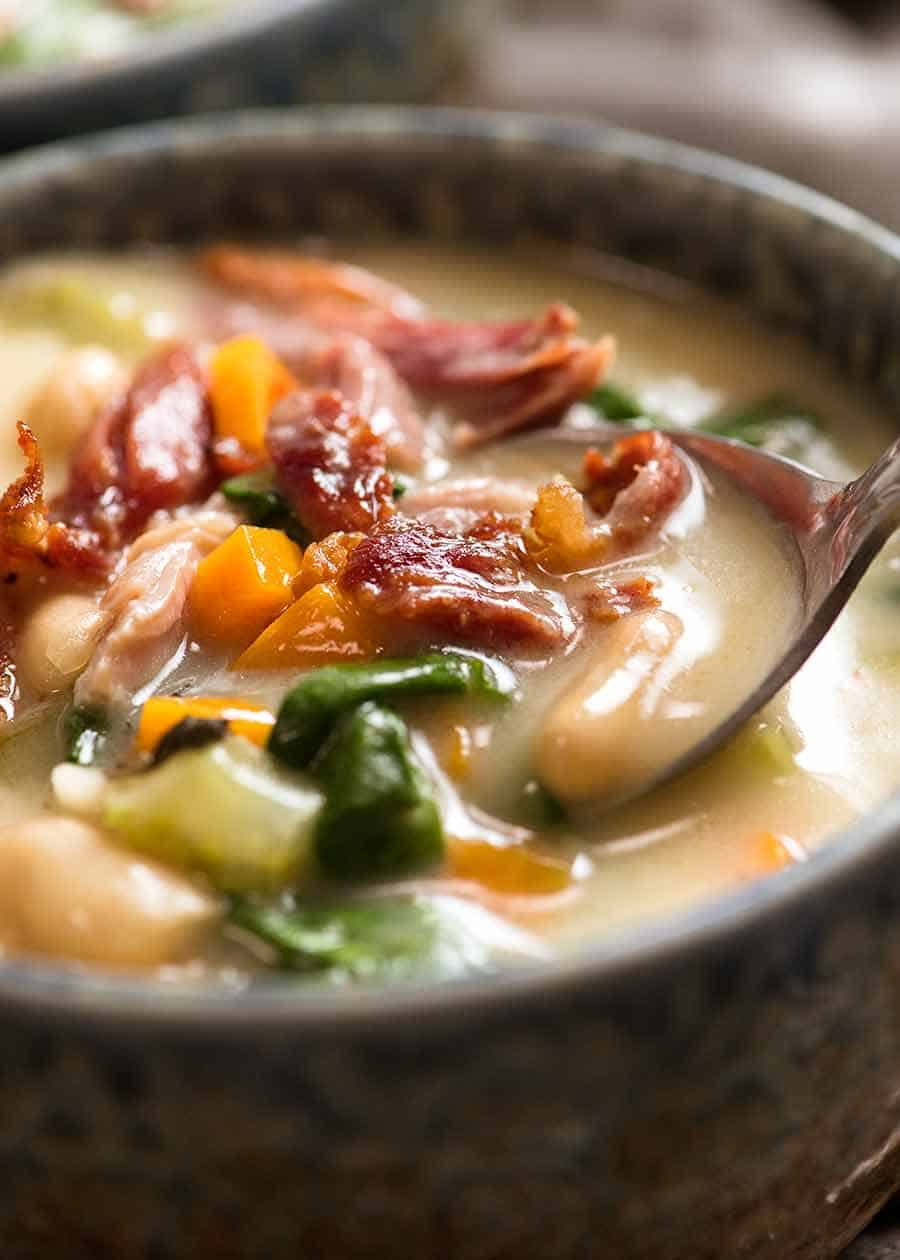 Close up of spoon dipping into bowl of Slow Cooker Ham Bone Soup with Beans