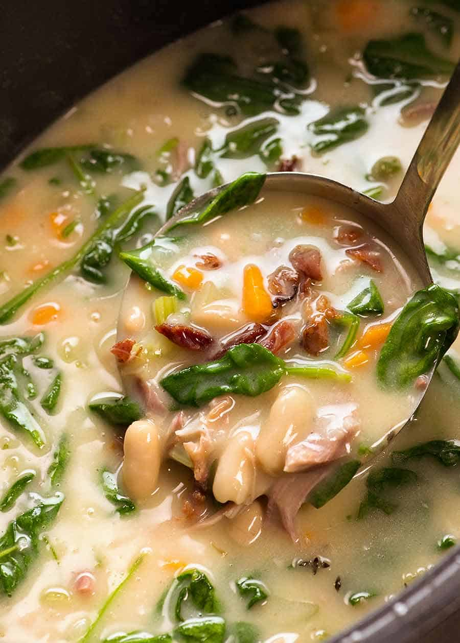 Close up of ladle scooping up Slow Cooker Ham Bone Soup with Beans