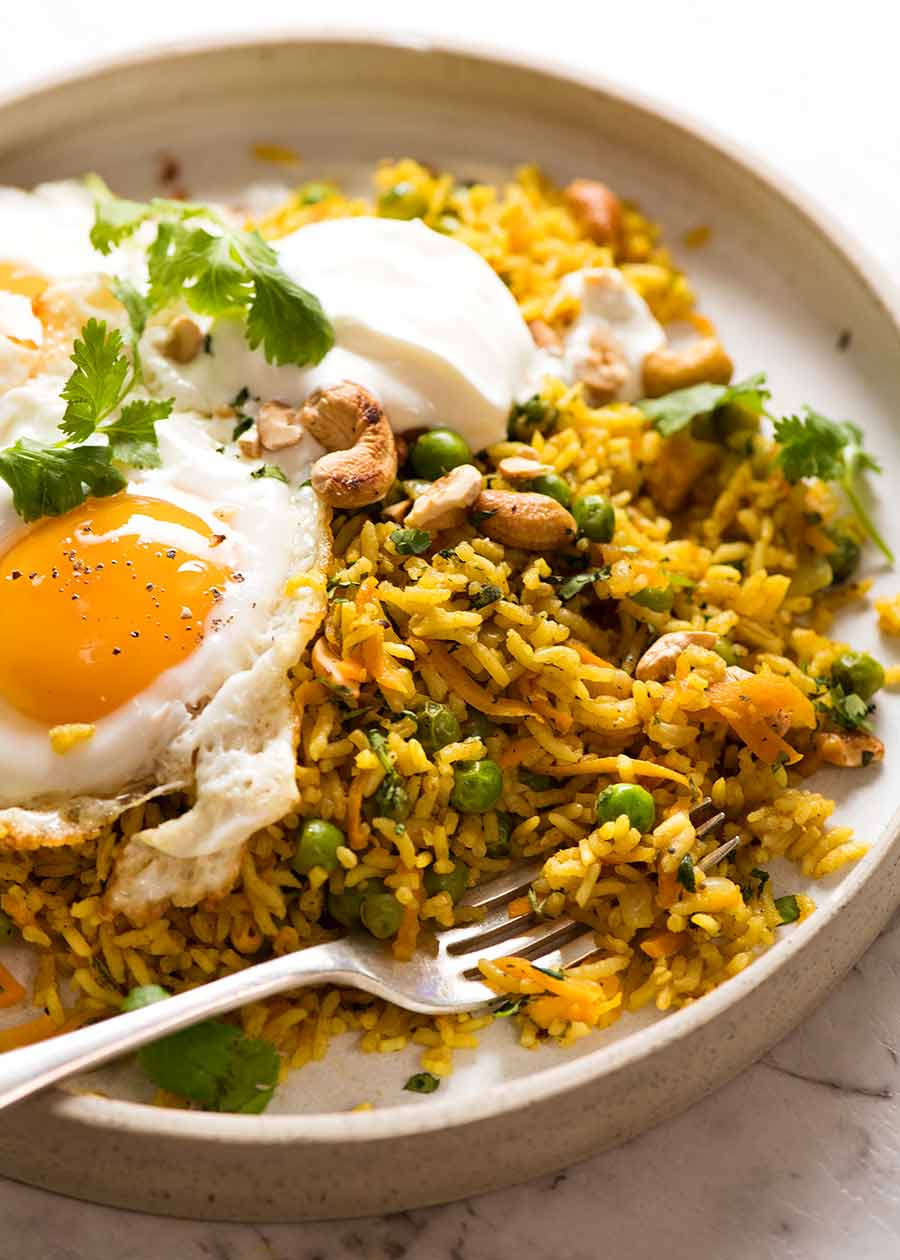 Close up of Curried Rice (basmati rice) with crispy fried egg and a dollop of yogurt on a rustic plate, ready to be eaten