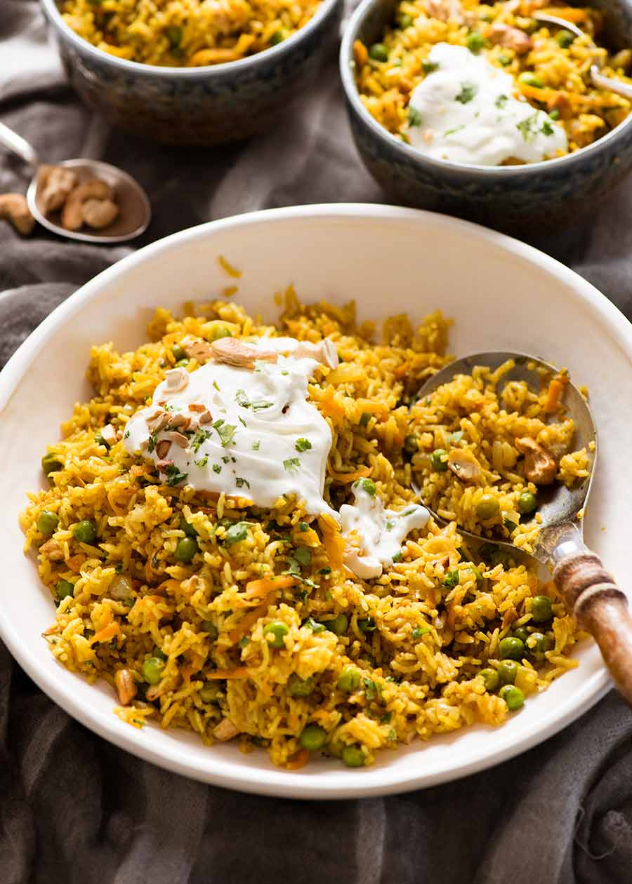 Curried Rice made with Basmati Rice in a white bowl being served