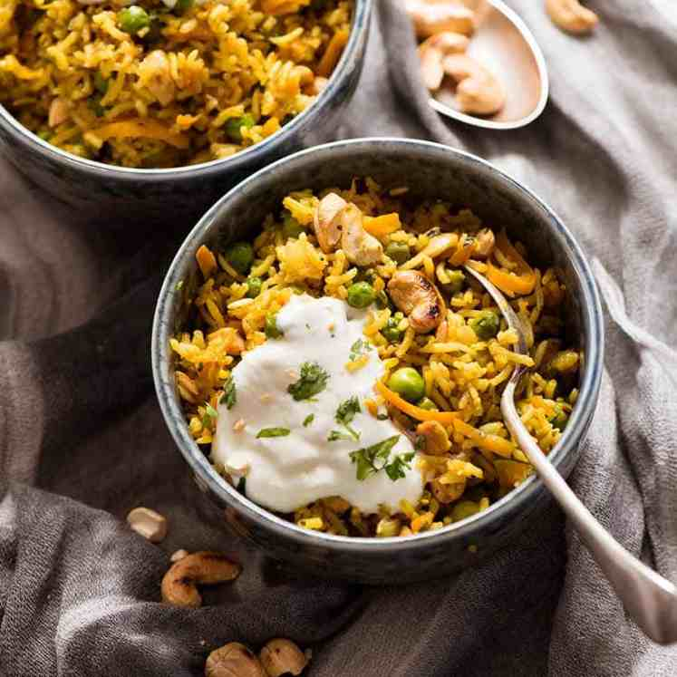 Two rustic bowls with Curried Rice made with Basmati Rice, topped with a dollop of yogurt