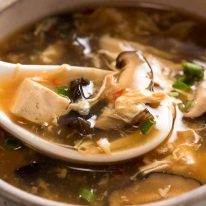 Close up of Chinese spoon scooping up Hot and Sour Soup from bowl