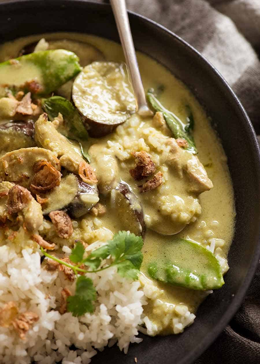 Close up of spoon scooping up Thai Green Curry with chicken served over rice