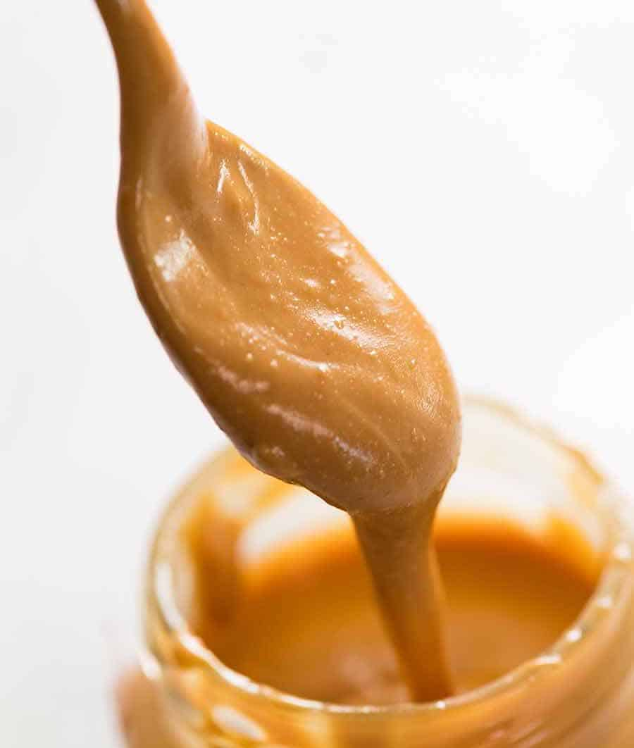 Spoon scooping pure, natural peanut butter from jar