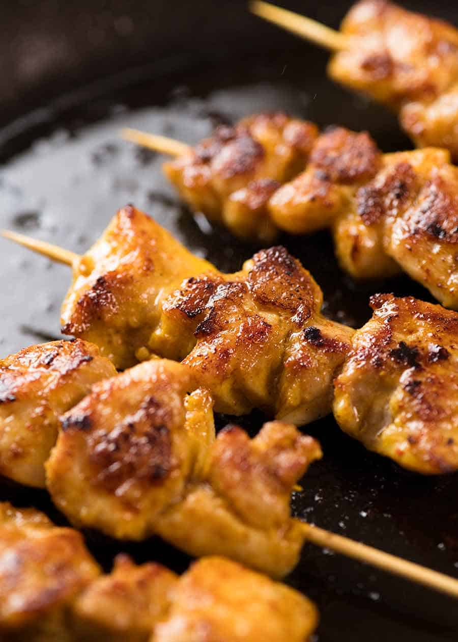 Thai Chicken Satay Skewers cooking in skillet