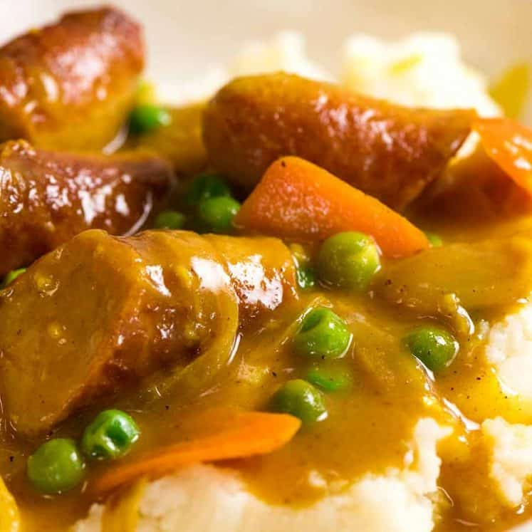 Curried Sausages over mash in a bowl, ready to be eaten