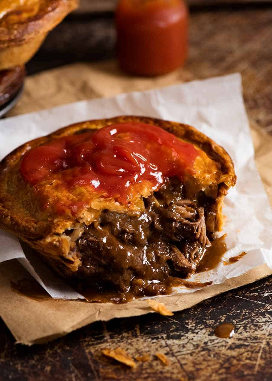 Close up of Meat Pie cut open to show meat pie filling inside, with tomato sauce on top