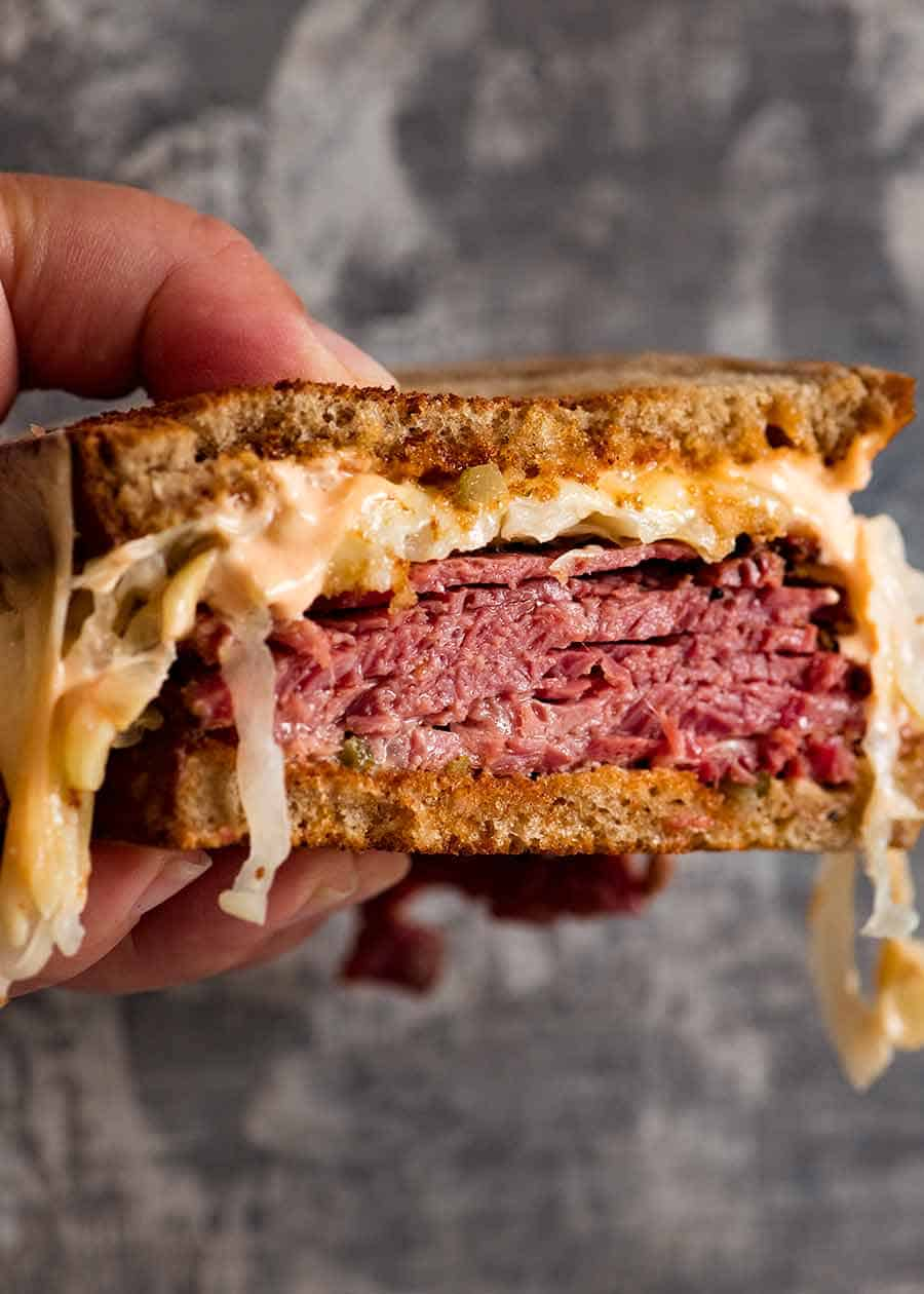 Reuben Sandwich loaded with homemade pastrami, easy quick sauerkraut, Russian Dressing, Swiss cheese on rye bread, ready to be eaten. Katz's deli copycat recipe.