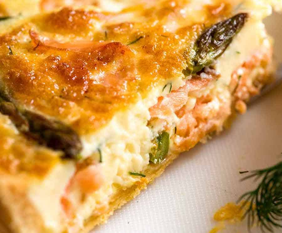 Slice of Salmon Quiche showing the custardy inside with flakes of salmon