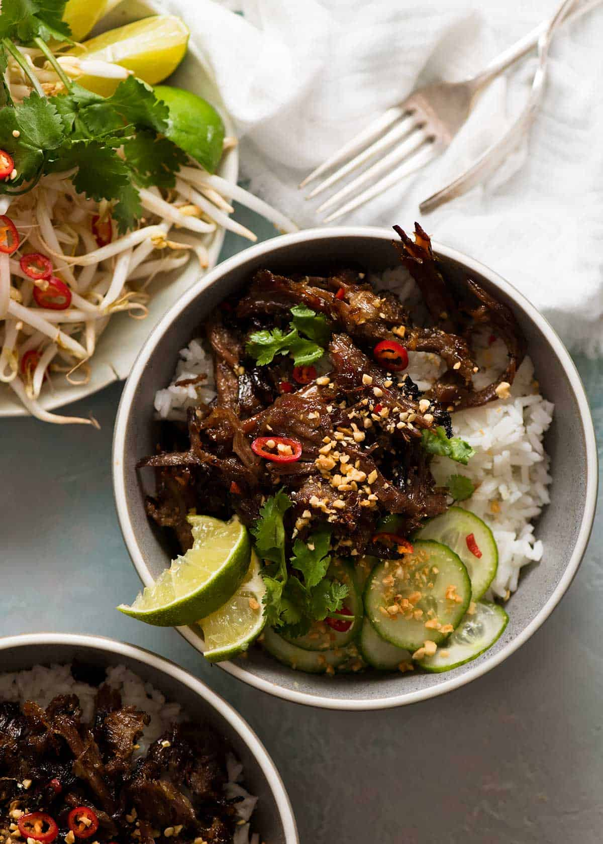 2 bowls of Caramelised Vietnamese Shredded Beef over rice with a side of bean sprouts and fresh herbs
