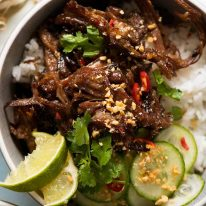 Overhead photo of Caramelised Vietnamese Shredded Beef served over rice with lime wedges, cucumber, chilli and peanuts