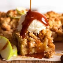 Apple Crumble Bars with ice cream and salted caramel sauce being drizzled over