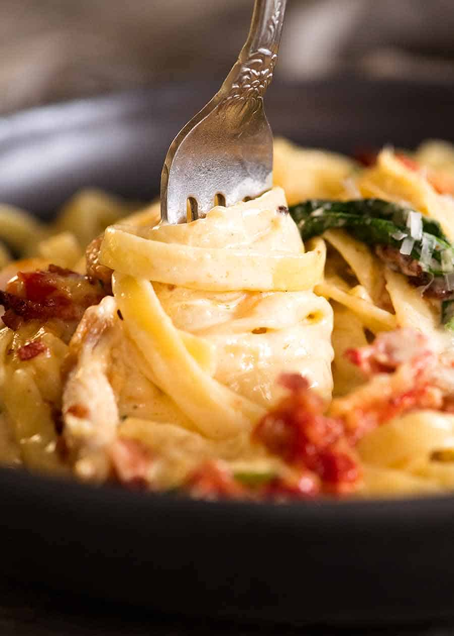 Close up of fork twirling creamy chicken pasta with sun dried tomato, spinach and bacon