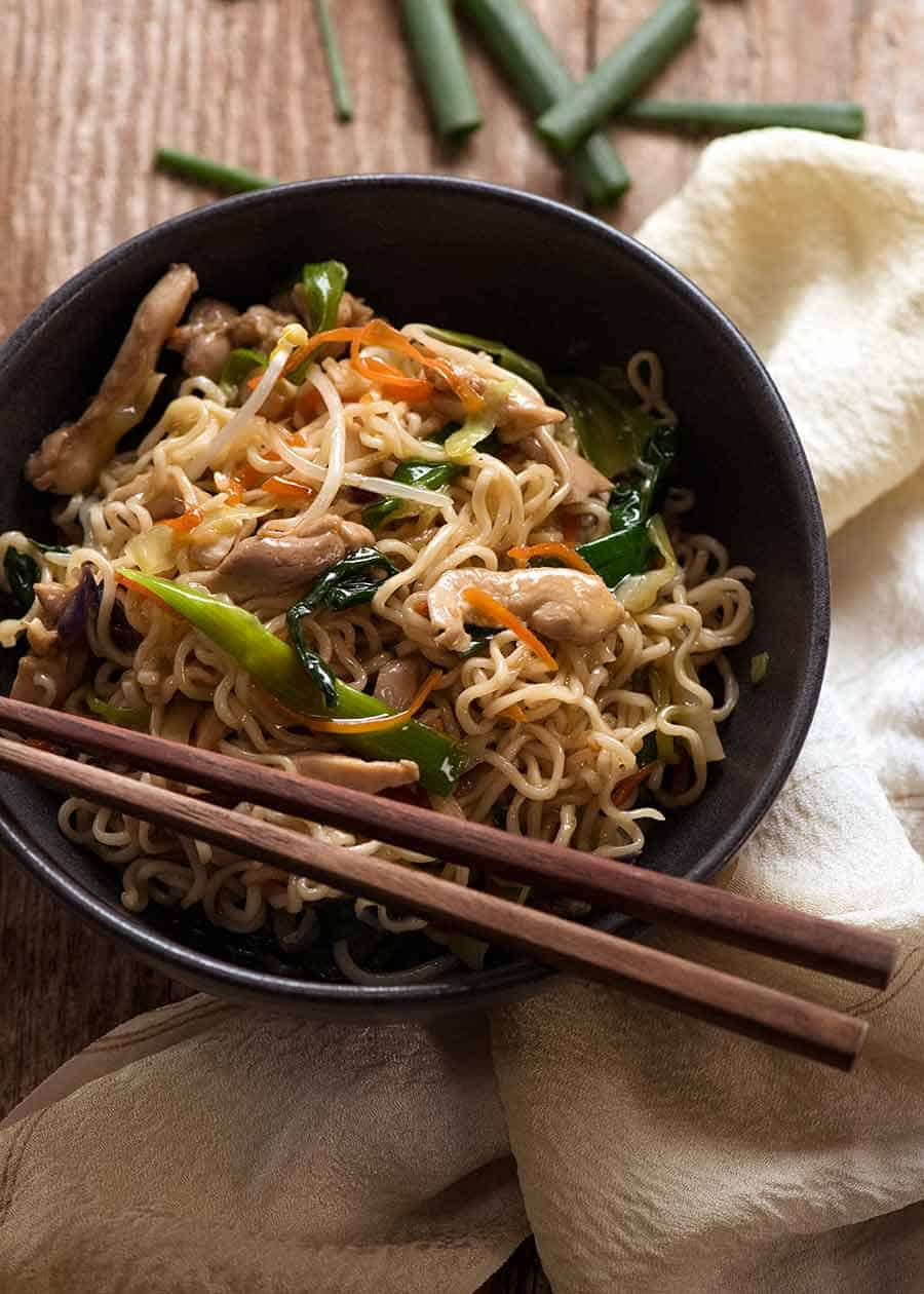 Chow Mein Ramen Noodles in a rustic black bowl with chopsticks, ready to be eaten