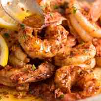 Close up of spoon drizzling Lemon Garlic Butter Sauce over grilled shrimp / prawns