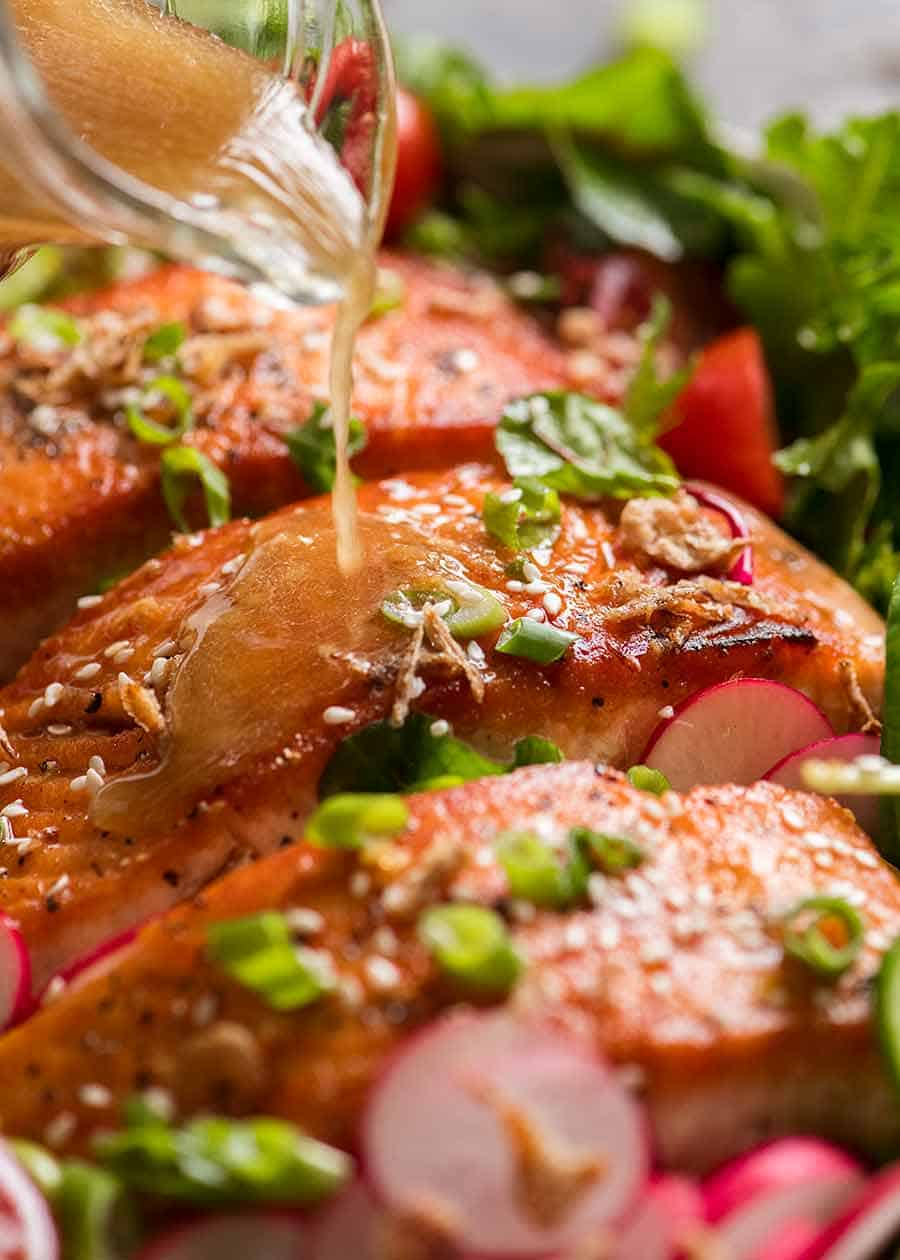 Asian Ginger Sesame Dressing being drizzled over Salmon Salad