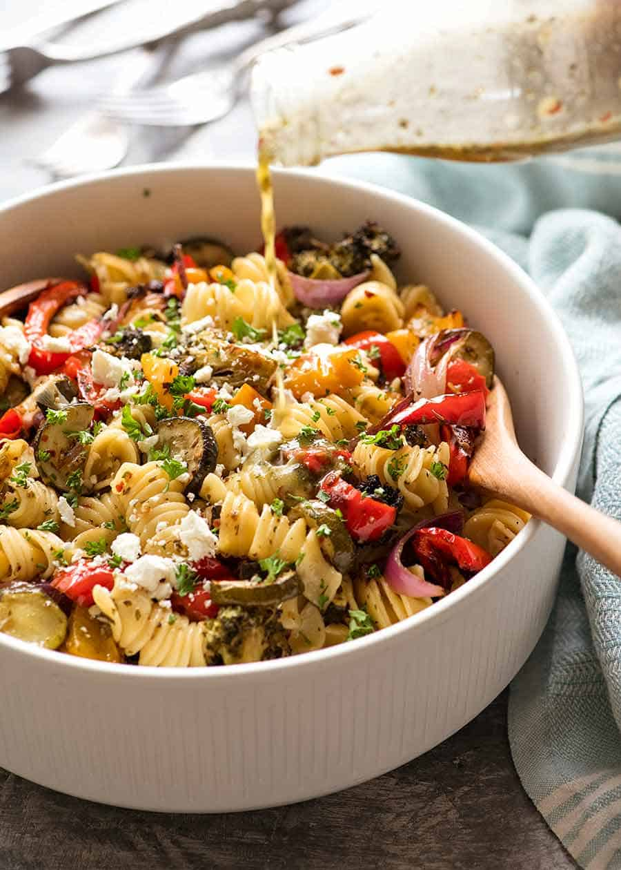 Pouring lemon garlic pasta salad dressing over Vegetable Pasta Salad