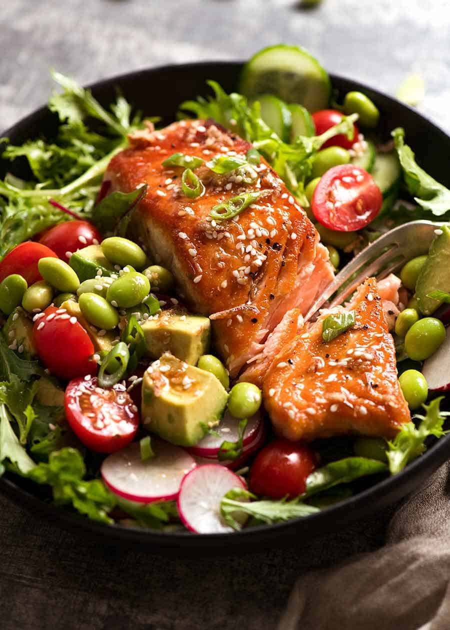 Close up of Asian Salmon Salad on a plate with edamame, avocado, tomato, radish and lettuce, with Asian Sesame Dressing