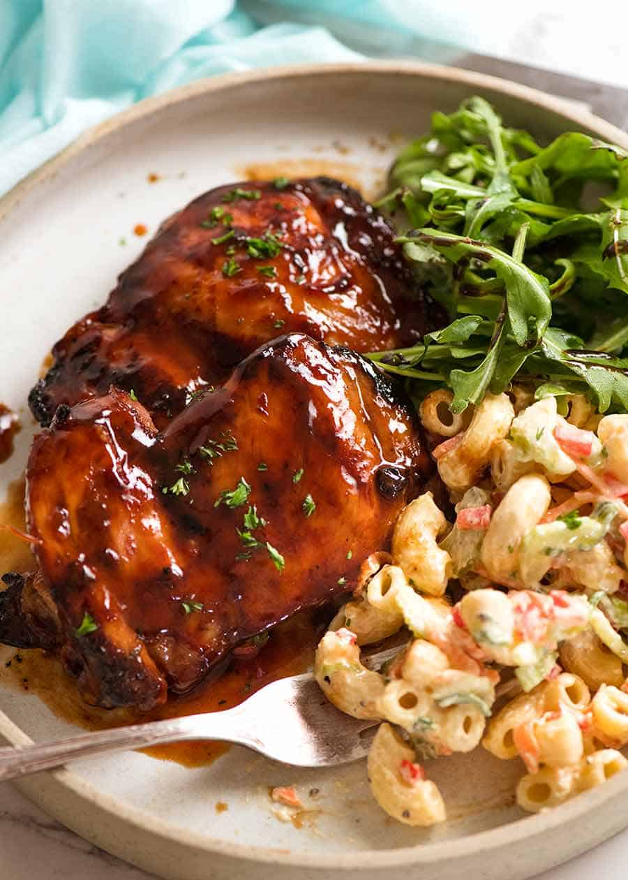 Sticky Grilled Chicken in a plate with a side of Macaroni Salad and Rocket Salad on a plate, ready to be eaten