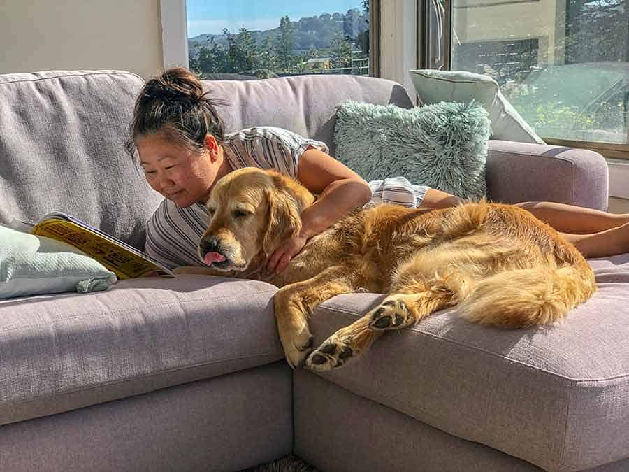 Nagi from RecipeTin Eats and Dozer the golden retriever on the couch