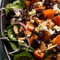 Close up of sweet potato salad with baby spinach, feta, almonds, red onion, wild rice drizzled with a Honey Lemon Dressing