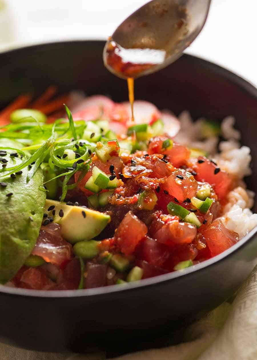 Drizzling dressing over Poke Bowl