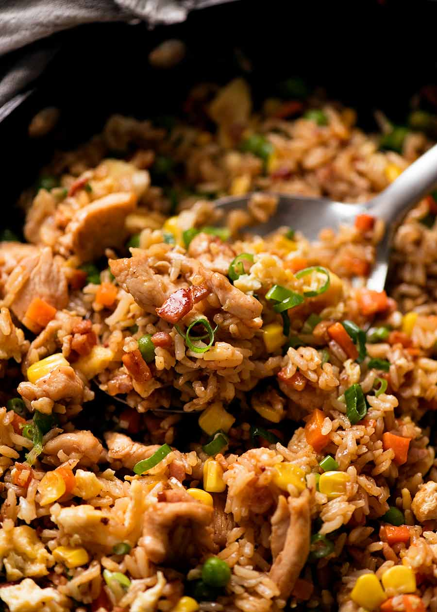Close up of Chicken Fried Rice with seasoned chicken, bacon, peas, carrots, corn and fluffy egg, ready to be served.